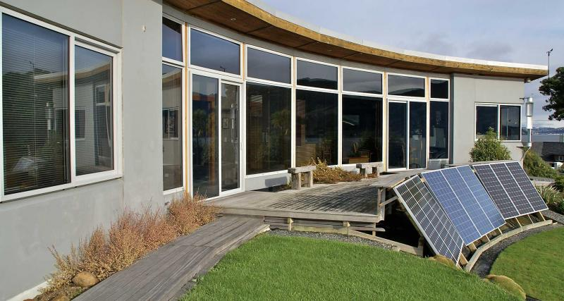 Exterior of house with solar panels in garden for power generation